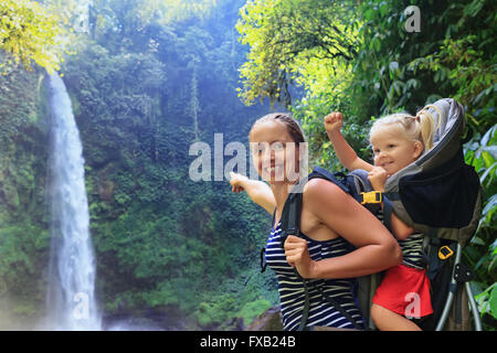 Mother hold baby girl on back in carrying backpack walking in waterfall canyon. - Stock Photo