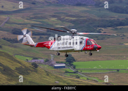 HM Coastguard helicopter operating in Snowdonia, North Wales. - Stock Photo