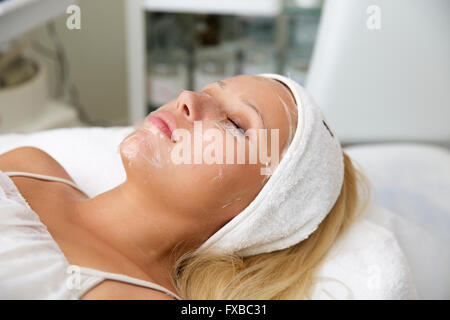 Beautiful young woman during facial massage in cosmetic salon close up - Stock Photo