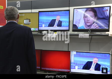 Moscow, Russia. 14th Apr, 2016. A man watches the televised question-and-answer session of Russian President Vladimir - Stock Photo