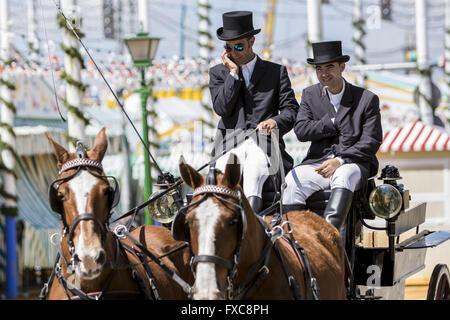 Seville, Spain. 14th Apr, 2016. Driver of typical chariot at the ''Feria de Abril'' (April's Fair) talks by phone - Stock Photo