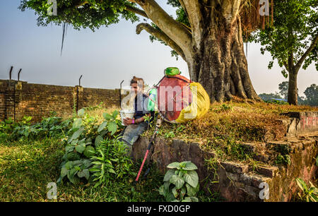 Wandering sadhu baba  (holy man) with traditional long hair and a huge bag - Stock Photo