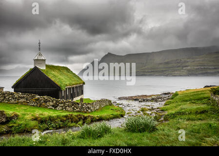Small village church in Funningur under heavy clouds. Funningur is located on the island of Eysturoy, Faroe Islands, - Stock Photo
