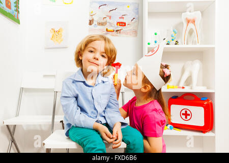 Cute ear nose throat specialist examining boy - Stock Photo
