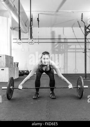 Photo of a young woman at a crossfit gym lifting a barbell. - Stock Photo