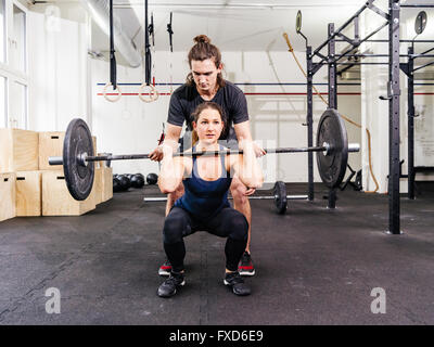 Photo of a young woman at a crossfit gym doing squats while her instructor watches from behind. - Stock Photo
