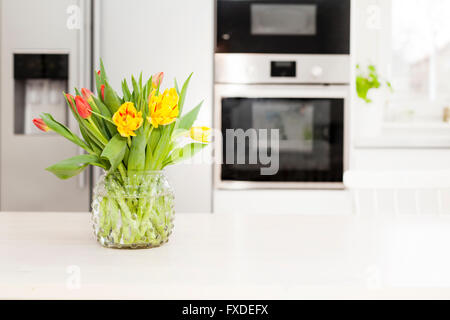 tulips in a vase on the table in fancy kitchen - Stock Photo