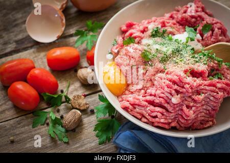 preparing beef steak tartare on bowl with egg - Stock Photo