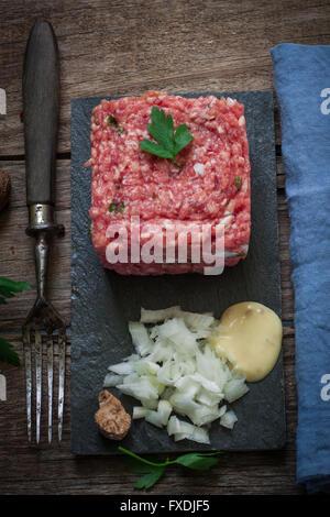 fresh beef steak tartare served on black tray - Stock Photo