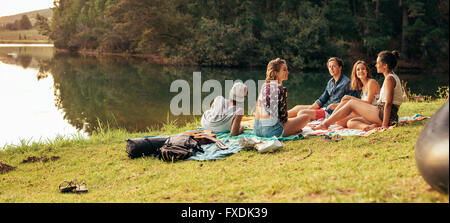 Young friends having picnic near a lake. Young friends enjoying a day at the lake. - Stock Photo