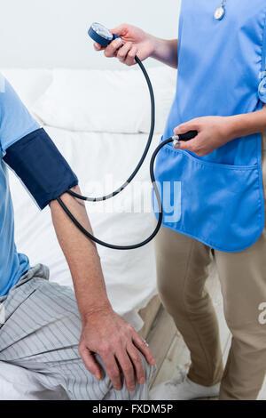 Female caretaker checking blood pressure of senior man at home - Stock Photo