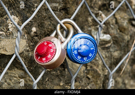 Two colored locks numerical combination, closed on a metal grid one inside the other - Stock Photo