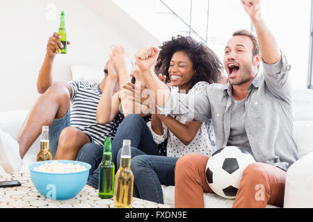 Excited friends cheering while watching television - Stock Photo
