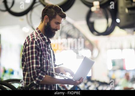 Bike mechanic checking laptop - Stock Photo