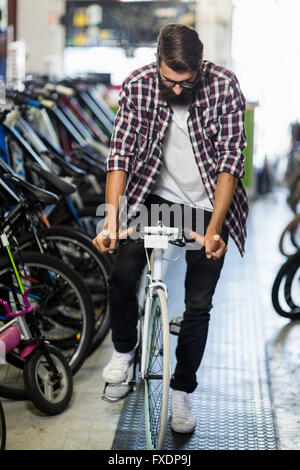 Cool hipster riding a bicycle - Stock Photo