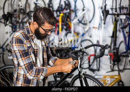 Bike mechanic checking at bicycle - Stock Photo