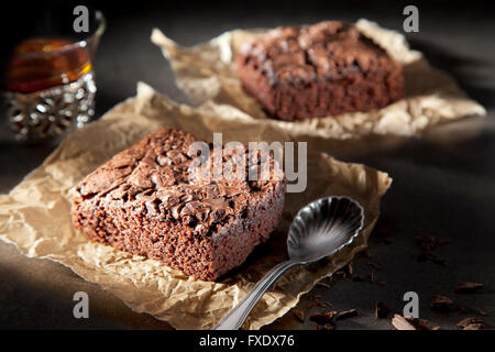Two brownies with chocolate sauce on paper with spoon and tea - Stock Photo
