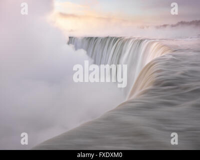Brink of Niagara Falls, Canadian Falls or Horseshoe Falls, at sunrise in winter, Niagara Falls, Ontario, Canada - Stock Photo
