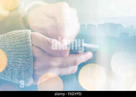 Man sending text message on smartphone, morning sunlight through the window, male hands using mobile phone device - Stock Photo