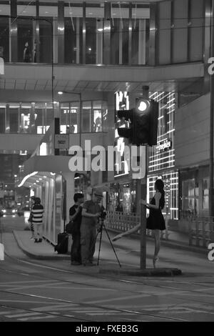 Ballerina (Ballet dancer) in the middle of the street in Hong Kong doing a photo shoot. black and white image. - Stock Photo