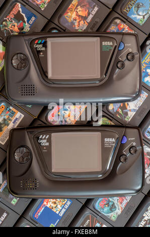 Two Sega Game Gear video game units - the original 1990 release and the Majesco version from 2001 - on a bed of - Stock Photo