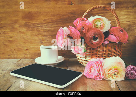 cup of coffee next to tablet and flowers on wooden table. vintage filtered and toned - Stock Photo