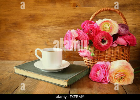 cup of coffee next to old book next to flowers on wooden table. vintage filtered and toned - Stock Photo