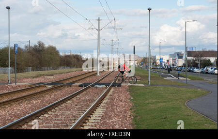 Edinburgh tramlines track,  rail section towards Arthur's Seat,  with cyclist on crossing point. - Stock Photo