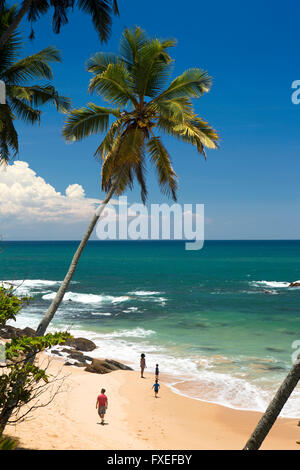 Sri Lanka, Tangalle, young family relaxing on idyllic tropical beach - Stock Photo