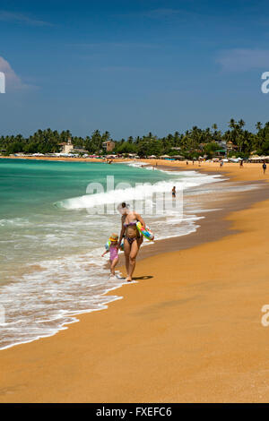 Sri Lanka, Unawatuna, mother and child walking along shore of new artificial sandy beach - Stock Photo