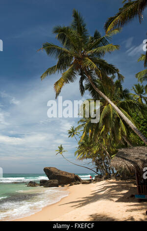 Sri Lanka, Unawatuna, Thalpe, Wijaya, couple crossing rocks on idyllic tropical beach - Stock Photo