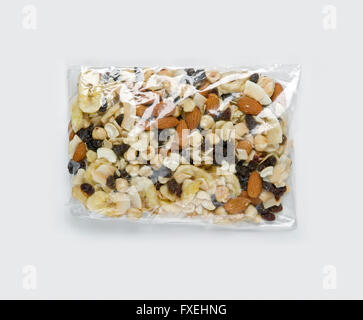 Assorted nuts and dried fruits in clear plastic bag, close-up - Stock Photo