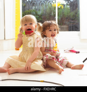 Two toddler girls sitting on floor eating ice lollies - Stock Photo
