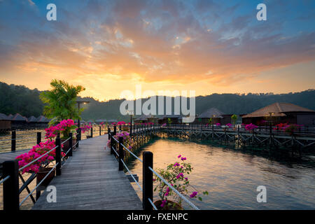 Over water bungalow at dusk.Beautiful sunset over beach with water villas in resort.Summer vacation concept - Stock Photo
