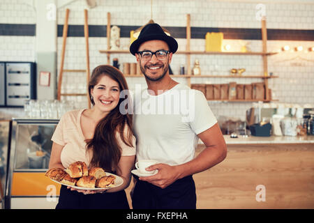 Portrait of happy young man and woman with food and cafe at coffee shop. Couple having food in a restaurant. - Stock Photo