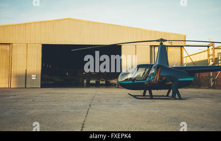 Helicopter pilot inspecting his aircraft  before take off. Helicopter is parked outside airplane hangar at airport. - Stock Photo