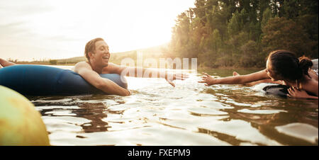 Loving young couple about to hold hands while floating on inner tubes in lake. Young man and woman on an inflatable - Stock Photo