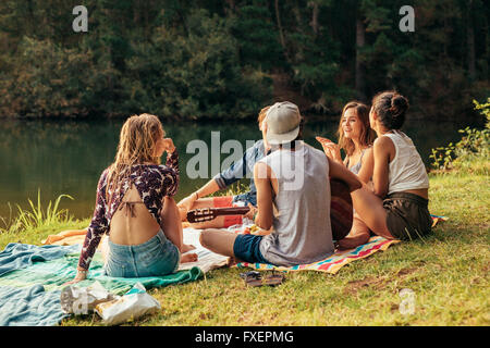 Young people having picnic near a lake. Young friends relaxing by a lake. - Stock Photo
