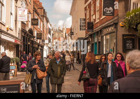 A view of the busy Stonegate street in the historic city of York,North Yorkshire,England,UK with York Minster in - Stock Photo