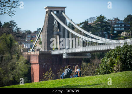 A couple enjoy the sunshine and warm temperatures next to the Clifton Suspension Bridge in Bristol.  P - Stock Photo
