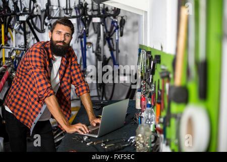 Bike mechanic checking at laptop - Stock Photo