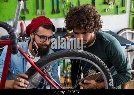 Bike mechanic talking to customer about the repairs - Stock Photo