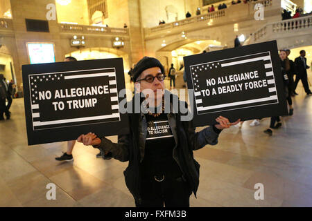 New York City, NY, USA. 14th Apr, 2016. A woman carrying anti-Trump signs stands in Grand Central Station. Hundreds - Stock Photo