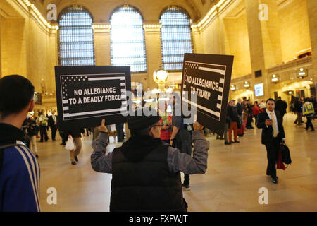 New York City, NY, USA. 14th Apr, 2016. Protesters carrying anti-Trump signs walk through Grand Central Station. - Stock Photo