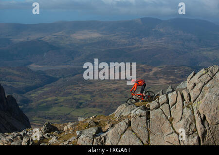 A mountain biker rides down from the summit of Cadair Idris in Snowdonia, Wales. - Stock Photo