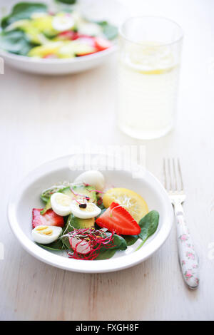 Baby spinach, avocado, lemon, strawberries and quail eggs salad - Stock Photo