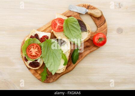 Open-faced sandwiches made of ciabatta, sun dried tomatoes, creamy cheese, arugula and lettuce leaf basil. Antipasti - Stock Photo
