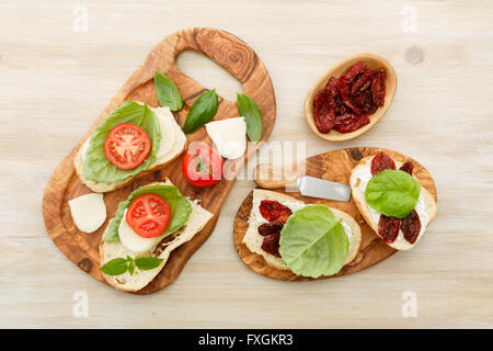 Open-faced sandwiches made of ciabatta, sun dried tomatoes, creamy cheese and lettuce leaf basil. Antipasti - Stock Photo