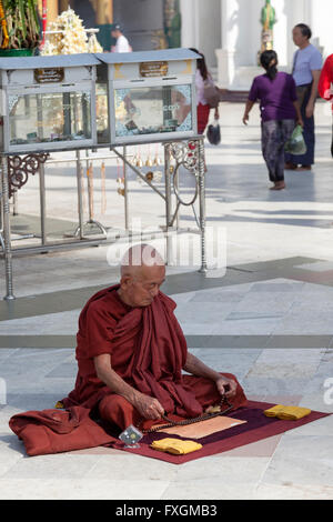 A cross-legged monk praying in front of an annex of the Paya Shwedagon, in Yangon (Myanmar). Moine assis en tailleur - Stock Photo