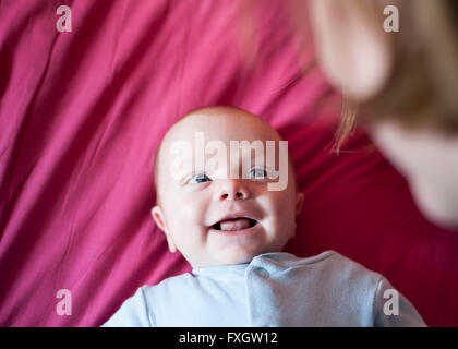 A cute newborn baby boy in a blue sleepsuit smiles at his mother who is out of focus - Stock Photo